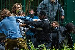 A National Eviction Team enforcement agent tries to block activists from HS2 Rebellion seeking to prevent or delay tree cutting in conjunction with the HS2 high-speed rail link in Denham Country Park on 7 September 2020 in Denham, United Kingdom. Anti-HS2 activists continue to campaign and take direct action against the controversial £106bn project for which the construction phase was announced on 4th September from a series of protection camps based along the route of the line between London and Birmingham.