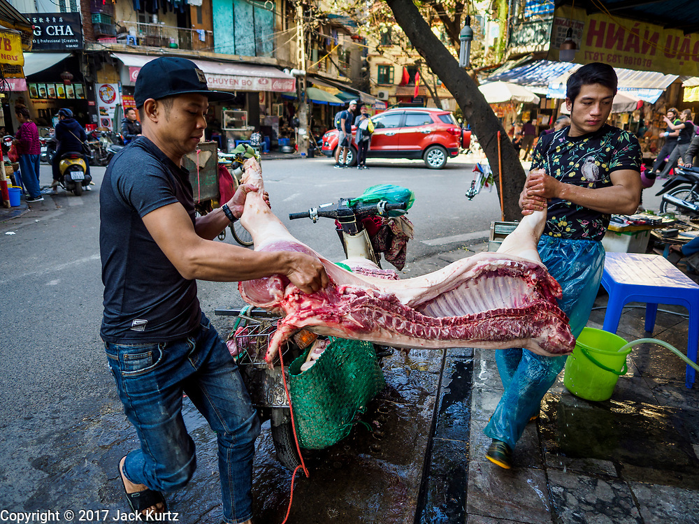 """21 DECEMBER 2017 - HANOI, VIETNAM: Men deliver a side of pork to a butcher shop in Hanoi's old quater. The old quarter is the heart of Hanoi, with narrow streets and lots of small shops but it's being """"gentrified"""" because of tourism and some of the shops are being turned into hotels and cafes for tourists and wealthy Vietnamese.   PHOTO BY JACK KURTZ"""