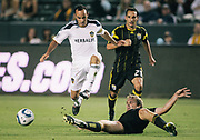Los Angeles Galaxy forward Landon Donovan, left, avoids a slide tackle by Columbus Crew defender Chad Marshall during the second half of an MLS soccer match, Wednesday, July 20, 2011, in Carson, Calif. The Galaxy won 1-0. (AP Photo/Bret Hartman)