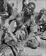 Young Karamajong girl and baby thrashing sunflower heads to remove the seeds - Near Moroto, Karamojo Uganda 1980 by Paul E Williams