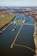 Nederland, Limburg, Gemeente Venlo, 07-03-2010; Sluis en stuwcomplex Belfeld, aangelegd in het kader van de kanalisatie van de Maas in de jaren 1918 - 1929. In de sluis wordt een schip geschut. Bij hoog water van de Maas kan het sluiscomplex overstromen, alle gebouwen staan op kolommen. .De stuw bestaat uit twee delen: schuiven die opgehesen kunnen worden (Stoney gedeelte) en schuiven op jukken (onder water, rechts, het Poiree gedeelte). Bij hoogwater worden de stuw 'gestreken' alle schuiven zijn dan omhoog respectievelijke verwijderd, scheepvaart is dan mogelijk door het geheel vrije stuwopening. .Lock and weir complex Belfeld, built in the context of the canalization of the Meuse in the years 1918 to 1929. A ship is locked through. .In case of high waters, the locks will be flooded, therefore the buildings are build on columns. The weir consists of two parts: slides that can be lifted (Stoney part) and slides on yokes (underwater, right, the Poirée part). At extreme high waters, the wie is 'lifted', all sliders are up respectively removed, shipping is possible through the completely free weir opening..luchtfoto (toeslag), aerial photo (additional fee required).foto/photo Siebe Swart