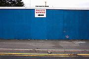 A Coke can lies in a gutter below a sign wanting pallets on an industrial roadside in West Thurrock, Thames gateway