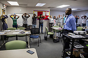 """Momen Alsaloum, 22, participates in a vocabulary exercise on his first day of English class with the CARIBE Refugee Program in Tampa, Florida, U.S. Teacher Jose Similus (front) would name a body part, in this case """"head,"""" prompting his students to point to it on themselves."""