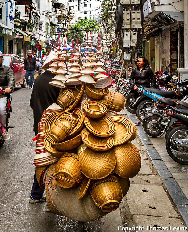 Street in Old Quarter, Hanoi, Vietnam, 3/27/17, Hat vendor on streets with bicycle and a pile of conical hats and bowls on the back.