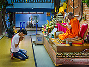 """30 DECEMBER 2017 - BANG KRUAI, NONTHABURI, THAILAND:  A monk blesses people in the basement of the prayer hall at Wat Ta Khien, about 45 minutes from Bangkok in Nonthaburi province. The temple is famous for the """"floating market"""" on the canal that runs past the temple and for the """"resurrection ceremonies"""" conducted by monks at the temple.      PHOTO BY JACK KURTZ"""