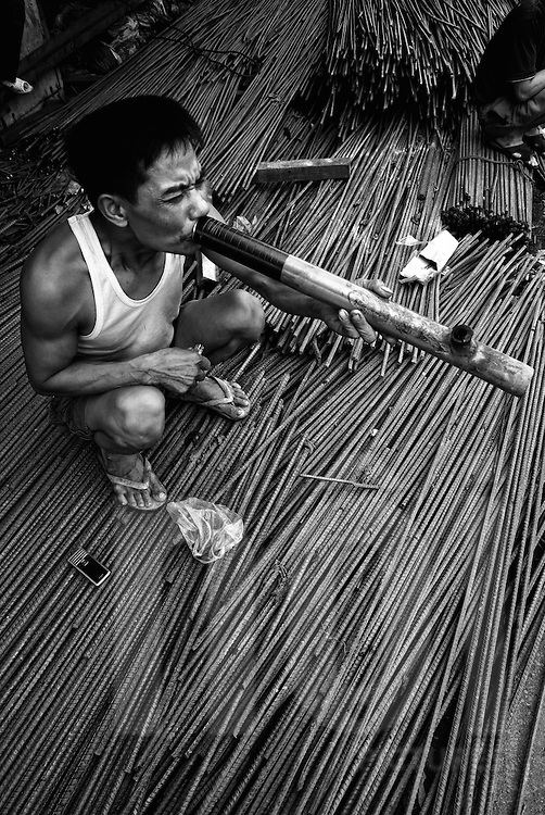 A Vietnamese worker sits on iron rods and deeply inhales smoke from a large pipe, Hanoi, Vietnam, Southeast Asia