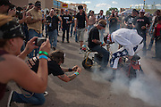 """Dressed as Evil Kenevil, Jesse Keierleber of Mesa AZ does a """"smokey burn-out"""" for the crowd following the Superhero mini-bike races event at the Smoke out motorcycle rally Santa Rosa NM on Saturday, June 19, 2010. A smokey burn-out is running the tread off the tire until the tire pops."""