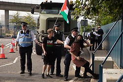 Metropolitan Police officers try to remove a human rights activist from an access road in front of a large military vehicle during a protest against the DSEI 2021 arms fair at ExCeL London on 6th September 2021 in London, United Kingdom. The first day of week-long Stop The Arms Fair protests outside the venue for one of the world's largest arms fairs was hosted by activists calling for a ban on UK arms exports to Israel.