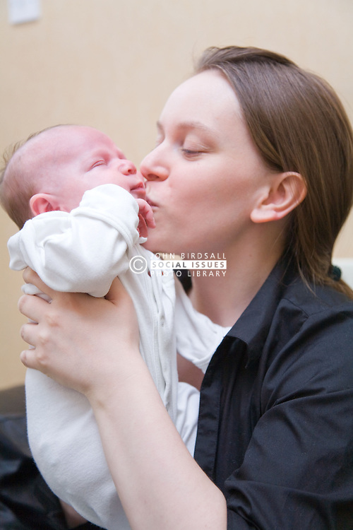Young mother kissing her new five week old baby,