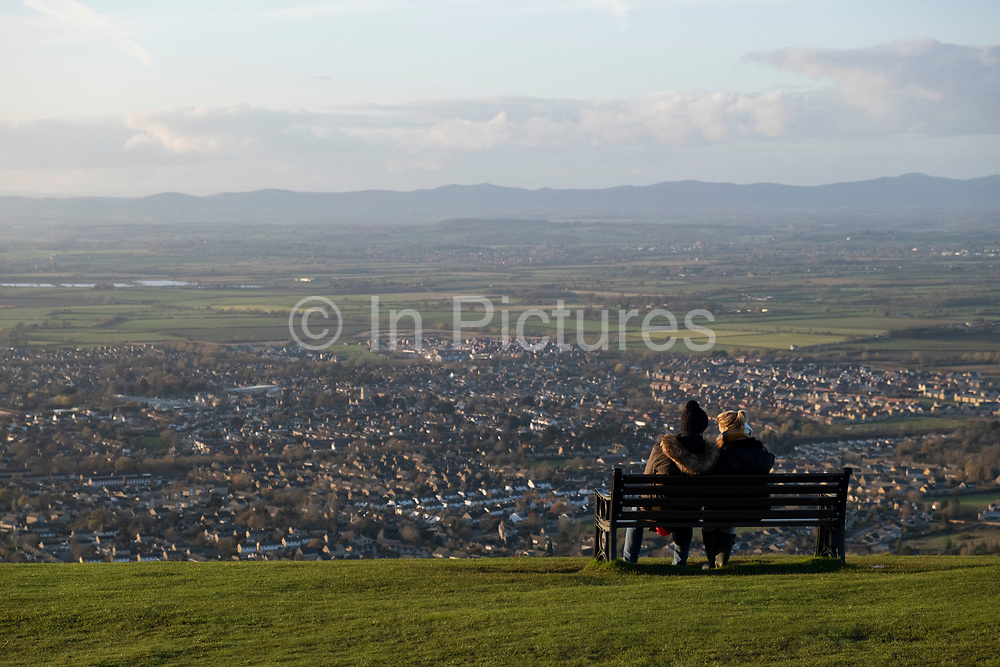 People take in the views across Gloucestershire towards Bishops Cleve from Cleve Hill on 22nd November 2020 in Cheltenham, United Kingdom. Cleeve Hill is the highest point both of the Cotswolds hill range and of the county of Gloucestershire, at 1,083 feet. It is located on Cleeve Common which is a Site of Special Scientific Interest looked after by a small charity called Cleeve Common Trust.