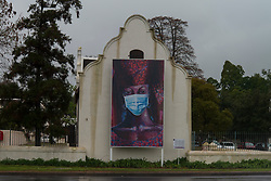 """""""The Senegal Woman"""" with a superimposed mask by Gerard Sekoto is one of five public art installations, called the """"Masked Masterpieces,"""" installed at various locations across Stellenbosch, Western Cape, seen here on a rainy Thursday afternoon, August 20, 2020. The installations feature portraits by famous South African artists and encourage passersby to wear masks in public. PHOTO: EVA-LOTTA JANSSON / RealTime Images"""