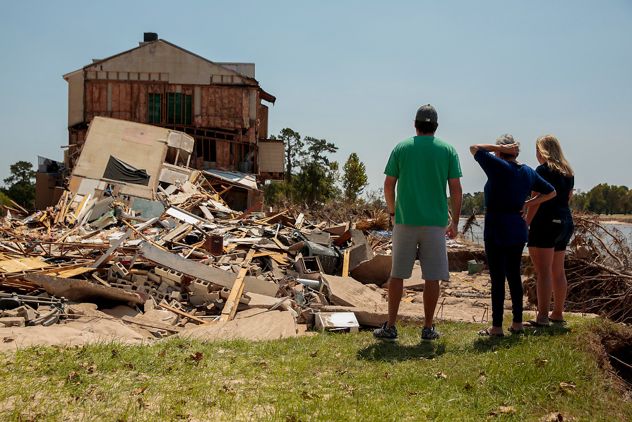 From left, Charlie Briganti, is joined by his mother-in-law, Juanita Hurt, and wife, Jenny Briganti as they look where their townhouse once stood on the San Jacinto River in the aftermath of tropical storm Harvey in Kingwood, Houston, Texas, U.S. September 9, 2017.