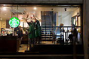 As customers talk, a Starbucks employee places a Christmas poster to the window of a coffee shop on Walbrook in the heart of the Square Mile, the capital's historical and financial centre, on 1st November 2017, in the City of London, England.