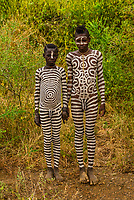 Mursi tribe boys with elaborate body chalk painting all over their bodies, Omo Valley, Ethiopia.