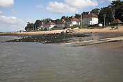 Beach and houses at Bawdsey Quay, Suffolk, England. These homes facing the tidal River Deben were once part of Ministry of Defence property at RAF Bawdsey. They are now mainly holiday homes.