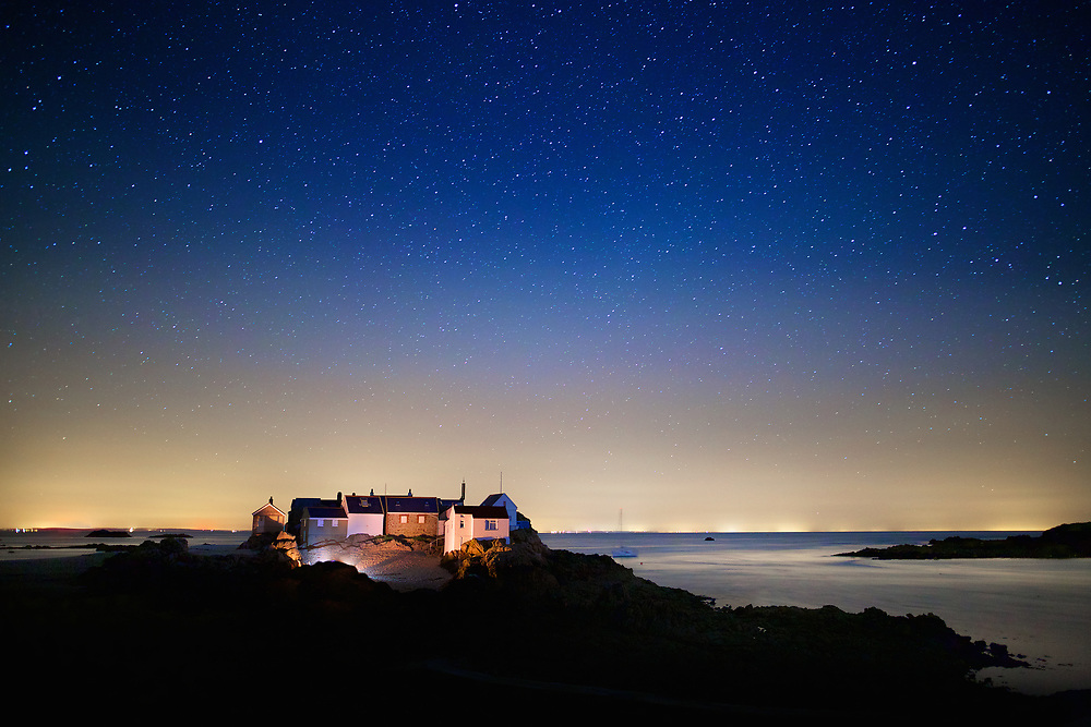 The houses at the Ecrehous lit up at night with the starry sky above and France lit up on the horizon line in the distance