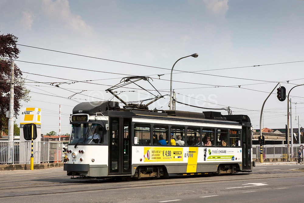 Passengers travel on a De Lijn electric tram on the road in Ghent, Belgium.  The trams have been modernized to use less electricity and become more sustainable public transport.