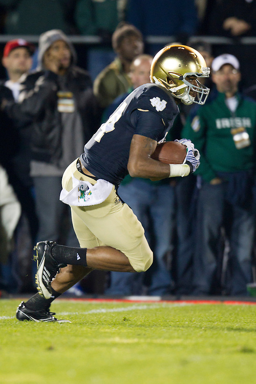 Notre Dame running back George Atkinson III (#34) initiates his second quarter touchdown run during NCAA football game between Notre Dame and USC.  The USC Trojans defeated the Notre Dame Fighting Irish 31-17 in game at Notre Dame Stadium in South Bend, Indiana.