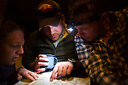 Backcountry skiers plan the next day's turns over a topo map at the Ridgway Hut, San Juan Mountains, Colorado.