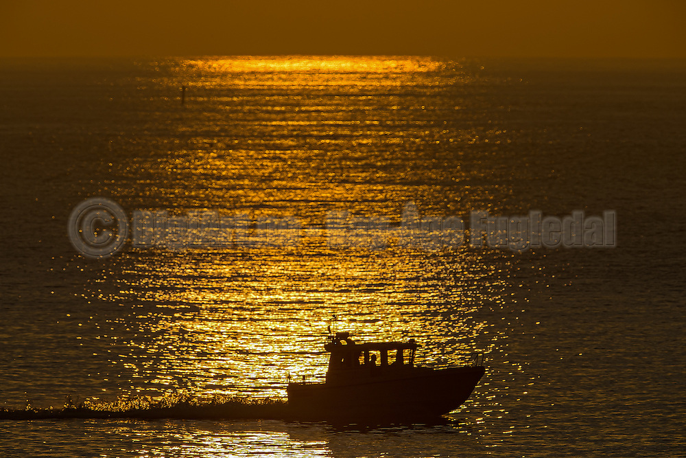 A silhouette of a boat driving through the reflections of the sunset in the sea | Silhuett av en båt som kjører gjennom refleksjonen av solnedgangen i sjøen.