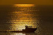 A silhouette of a boat driving through the reflections of the sunset in the sea   Silhuett av en båt som kjører gjennom refleksjonen av solnedgangen i sjøen.