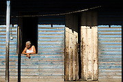 An elderly woman looks through the window of her home in Baracoa, Cuba on Monday July 14, 2008.