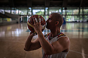 """2016/04/19 – Medellín, Colombia: Oscar Rios, 42, prepares to throws the ball to the basket during the training warm-up session of Antioquia's team at Atanasio Girardot Stadium, Medellin, 19th March, 2016.  <br /> -<br /> After his military service Oscar started to work as a bodyguard for a public prosecutor, a time of great violence in Medellin, during the 1990's when Pablo Escobar ran the city. <br /> On an assassination attempt of the public prosecutor, Oscar was shot seven times by Escobar's assassins. As a result he lost the mobility of his legs and feet, becoming paraplegic. <br /> The adaptation to a new life was hard, but he decided that he had to separate the injury under his waist from his head, and to keep doing what he wanted. Oscar had always liked basketball, so he decided to dedicate himself to it. In 1998 he became part of Team Colombia on wheelchair basketball. During his successful career he was several time South American Champion, was with Colombia on the top ten teams at the 2014 World Championship in Korea and went to the 2012 Paralympic Games in London. Unfortunately, this year Colombia missed the qualification for the Rio 2016 Paralympic, which was Oscar last opportunity to be back at an Olympics. <br /> He plans to retire soon and became a full-time basketball coach. Oscar believes that there is much talent in Colombia that needs to be fostered. When asked about the accident and his life on the wheelchair, Oscar says, """"Before I was an arrogant person and didn't have any love to give to my family. The accident was a blessing that made me a better, happier man and to appreciate more my life and family. If I was going to be born tomorrow, I wanted to be born on a wheelchair"""". (Eduardo Leal)"""