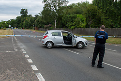 © Licensed to London News Pictures. 27/07/2021. Stoke Poges, UK. A police vehicle blocks the road at the scene on Bells Hill in Stoke Poges, Buckinghamshire, following an assault on Monday 26 July at approximately 21:30BST. A man in his twenties suffered a serious leg injury following the assault which is understood to have involved a machete. Two men, aged 19 and 21, and a 20-year-old woman have been arrested on suspicion of section 18 wounding with intent. Photo credit: Peter Manning/LNP