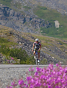 Alaska. Bike racer climbing through Thompson Pass in the Fireweed 400 race to Valdez along the Richardson Highway, July 2009, with Worthington Glacier in the background.
