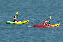 © London News Pictures. United Kingdom, Swanage : A man and woman canoe along the sea on a hot day in Swanage, Dorset, on June 3, 2015. . Photo credit: LNP