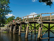 People walk across the Old North Bridge over the Concord River while exploring Minute Man National Historic Site, Concord, Massachusetts, USA.