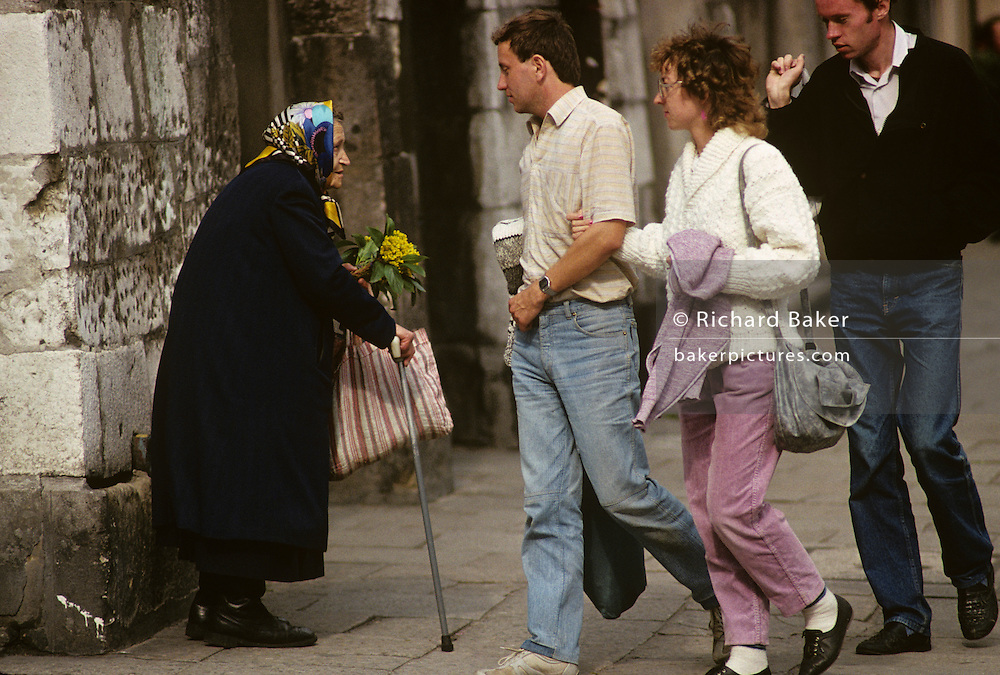 An unfortunate and hunched, elderly woman sells flowers to uncaring young passers-by on a Krakow street corner, Poland.
