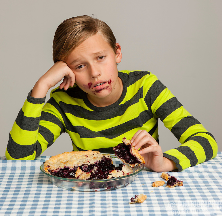 Boy eating too much pie