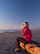 A woman sits on a log enjoying a glass of white wine and sunset; Hokitika, New Zealand