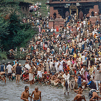Higher caste Hindus gather for ritual purification in the Bagmati River at the 1977  Genai Pherni festival at Gokarna Temple in the Kathmandu Valley, Nepal.