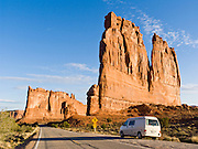 """The orange sandstone Courthouse Towers resist erosion in Arches National Park, Utah, USA. These rock monuments are beautiful both at sunrise (seen here) and sunset. A Volkswagon Eurovan Camper parks at a pullout. Published in """"Light Travel: Photography on the Go"""" by Tom Dempsey 2009, 2010."""
