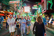 "26 SEPTEMBER 2014 - PATTAYA, CHONBURI, THAILAND: Tourists on Walking Street, the red light district in Pataya. Pataya, a beach resort about two hours from Bangkok, has wrestled with a reputation of having a high crime rate and being a haven for sex tourism. After the coup in May, the military government cracked down on other Thai beach resorts, notably Phuket and Hua Hin, putting military officers in charge of law enforcement and cleaning up unlicensed businesses that encroached on beaches. Pattaya city officials have launched their own crackdown and clean up in order to prevent a military crackdown. City officials have vowed to remake Pattaya as a ""family friendly"" destination. City police and tourist police now patrol ""Walking Street,"" Pattaya's notorious red light district, and officials are cracking down on unlicensed businesses on the beach.     PHOTO BY JACK KURTZ"