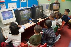 Group of primary school children using computers and watching televisions in classroom,