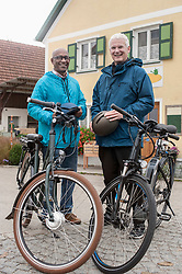 Happy male friends with cycling helmet on their bicycles, Bavaria, Germany