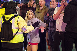 """© Licensed to London News Pictures . 16/12/2017. Manchester, UK. A man , believed to have been injured in a fight with another man , stems blood flowing from his nose as a friend wearing a blood-stained sweat shirt, hails a taxicab . Revellers out in Manchester City Centre overnight during """" Mad Friday """" , named for historically being one of the busiest nights of the year for the emergency services in the UK . Photo credit: Joel Goodman/LNP"""