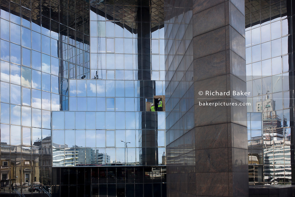 Surrounded by mirrored glass, two city workmen work high on a ledge of a modern city office block.
