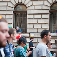 Local residents watch from their windows as participants of the Gay Pride Parade march in front of their hosue in Budapest, Hungary on June 18, 2011. ATTILA VOLGYI