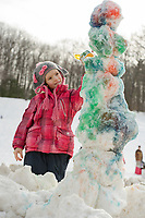 """Lorelai Shepherd decorates her snowman with a """"Picasso-like"""" style during Laconia Parks and Recreation snow building activity on Thursday afternoon.  (Karen Bobotas/for the Laconia Daily Sun)"""