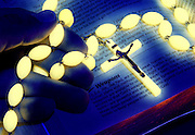 Hands holding a glowing crucifix on a bible.Black light