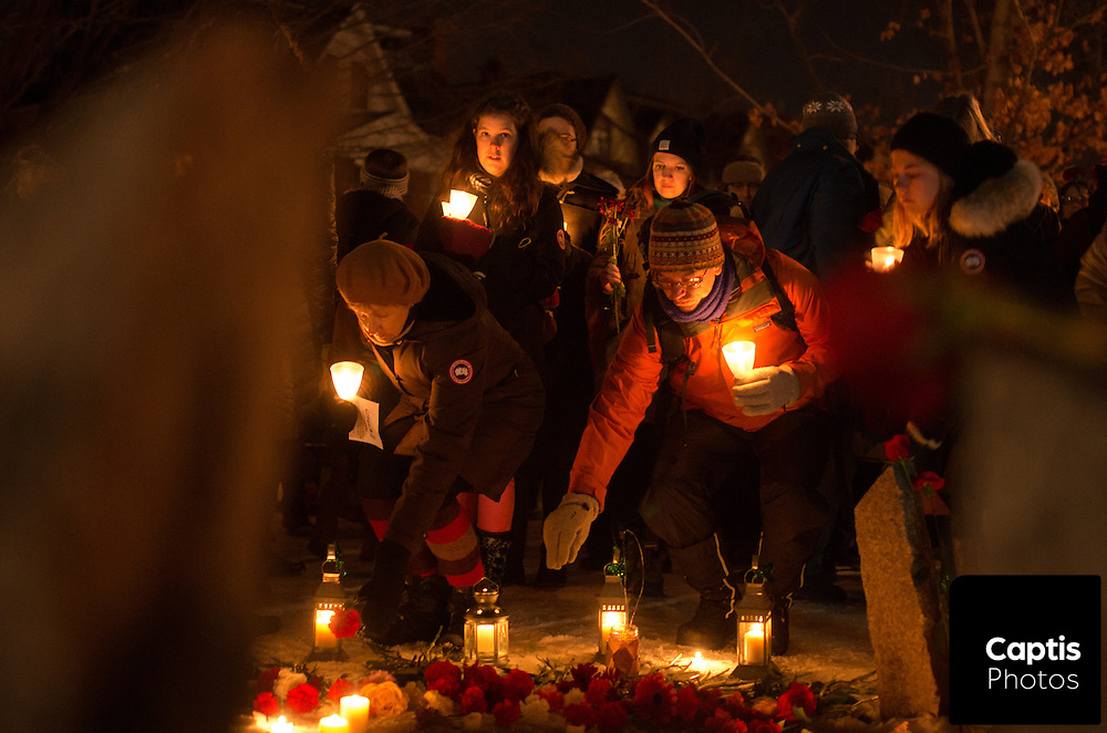 People place roses in front of the Women's Monument in Minto Park during the vigil. December 6, 2014.