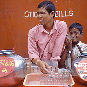 Rs. 2 is all you need for a glass of Masala Chach (buttermilk), and Rs. 3 if you fancy a glass of Madhur Lassi (Sweet Lassi).  A street vendor and his young playful assistant near Mohammed Ali Road,.Mumbai, March 2006
