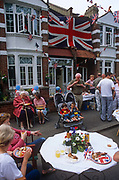 A giant Union jack hangs from an Edwardian house as neighbours hold a street party in honour of Queen Elizabeths Golden Jubilee celebrations, on 3rd June 2002, in Herne Hill, south London, England.