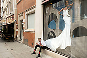 Man smoking a cigarette and looking at his smartphone as he sits outside a bridal wear shop on Bond Street on 25th May 2021 in London, United Kingdom. These high end brands are seen next to each other on a very ordinary wall. Bond Street is one of the principal streets in the West End shopping district and is very upmarket. It has been a fashionable shopping street since the 18th century. The rich and wealthy shop here mostly for high end fashion and jewellery.