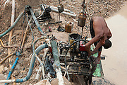The hidden side of high tech smartphones. Miner works in a huge illegal tin mine in Batako, Tunghin, that has completely devastated the once green landscape. Bangka Island (Indonesia) is devastated by a deadly tin rush, a direct consequence of the success of smartphones and tablets like iPhones and iPads from Apple or Samsung. The demand and price for tin has increased due to its use in smart phones and tablets.<br /> <br /> Le côté caché du succès des smartphones. Des mineurs travaillent dans une grande mine d'étain illégale à Batako - Tunghin qui a complètement dévasté un paysage qui était autrefois verte. L'île de Bangka (Indonésie) est dévastée par des mines d'étain sauvages, une conséquence directe du succès des smartphones et tablettes comme les iPhones et les iPads d'Apple ou Samsung. La demande de l'étain a explosé à cause de son utilisation dans les smartphones et tablettes.