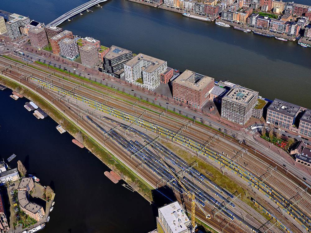 """Nederland, Noord-Holland, Amsterdam; 23-03-2020; Piet Heinkade met emplacement van de NS (Rietlanden). Oostelijke eilanden met IJhaven en Veemkade, Dijksgracht (links).<br /> Door de Coronacrisis is er weinig verkeer en omdat de NS een speciale basisdienstregeling ingevoerd, zijn veel treinen 'geparkeerd' op opstelsporen. <br /> Piet Heinkade with railway yard of the NS (Rietlanden). Eastern islands with IJhaven and Veemkade, Dijksgracht (right).<br /> Due to the Corona crisis, there is little traffic and because the NS has introduced a special basic timetable, many trains are """"parked"""" on Railway yard.<br /> <br /> luchtfoto (toeslag op standaard tarieven);<br /> aerial photo (additional fee required)<br /> copyright © 2020 foto/photo Siebe Swart"""